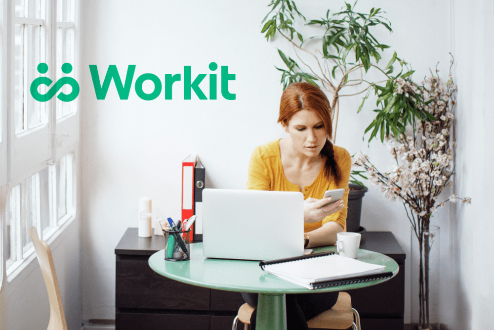 A woman sitting at a laptop works on her phone. addiction startup seed funding