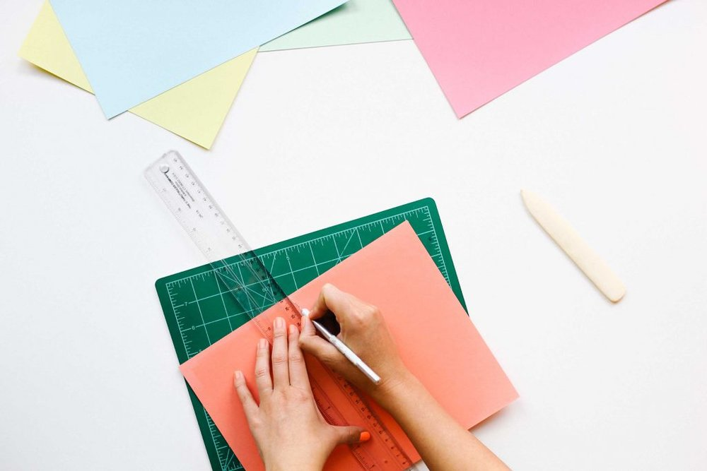 Cutting paper with a ruler and craft knife. Naming Workit Health