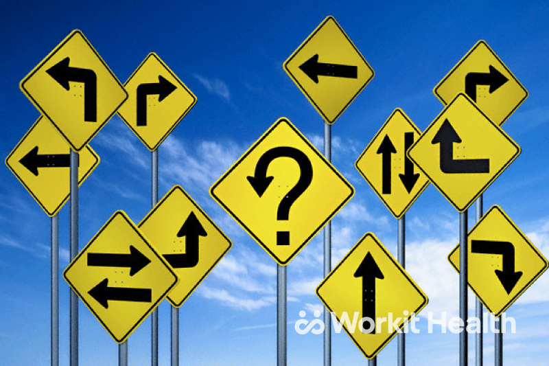 A collection of yellow traffic signs, all with arrows pointing in different directions, in front of a blue sky