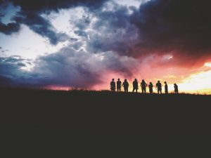 Nine people stand atop a hill, silhouetted by the rising sun