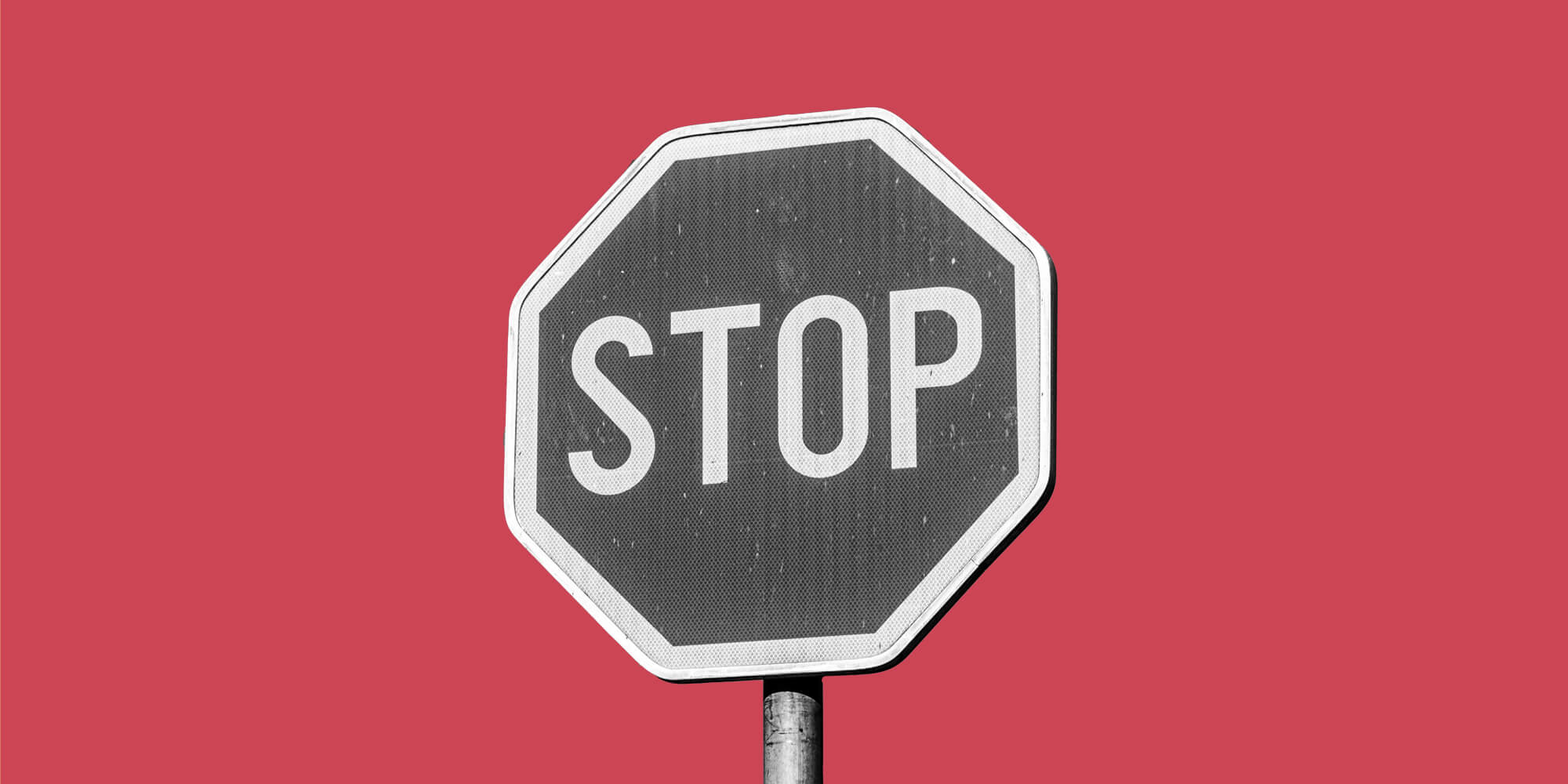 A grayscale STOP sign on a red background
