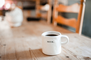 """Coffee mug with the word """"begin"""" pressed into the ceramic. Signature non-alcoholic drink"""