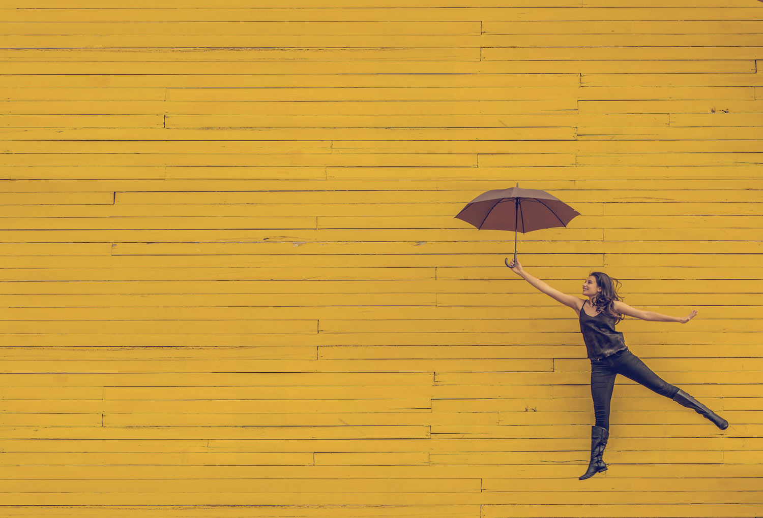 woman-jumping-with-umbrella-yellow-wall