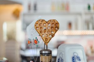 A heart-shaped waffle stands upright on a stick in a cheerful kitchen.