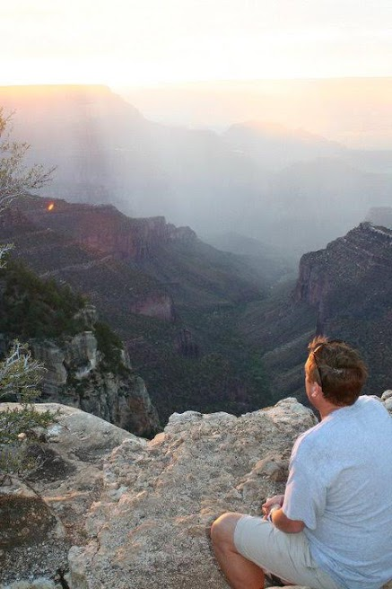 Kip Shubert, founder of Warriors on Purpose, sits on a mountain looking at the sunrise