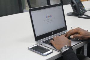 A black man on a laptop using Google