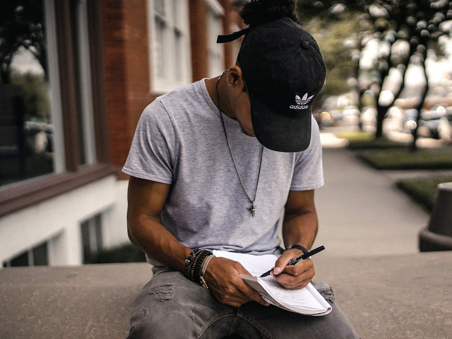 A man sits outdoors, writing in a notebook balanced on his leg