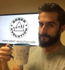 """Austin Cooper of Sober Evolution holds a coffee mug that reads """"Sober since 4/10/13"""""""