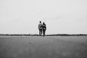 Black and white photo of a man and woman walking down an empty road with their arms around on another