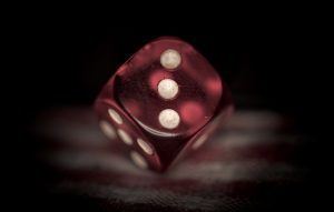 A red plastic die, showing three pips