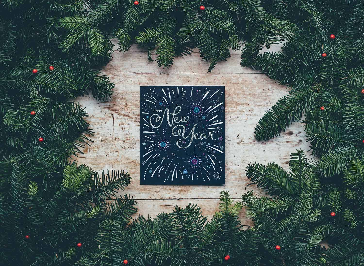 """A hand-lettered sign reading """"New Year"""" is surrounded by pine branches. Practical New Year's resolutions"""
