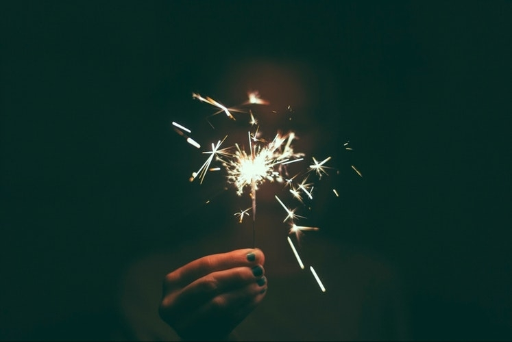 A hand holds a lit sparkler in the dark