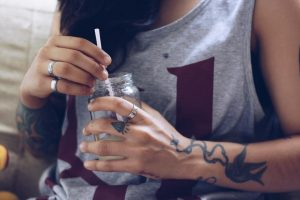 A woman with tattoos holds a drink in a mason jar. Pain Med Recovery