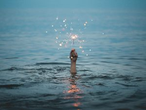 A hand reaches up out of the water, holding a lit sparkler. The rest of the body is submerged. Negative self talk.