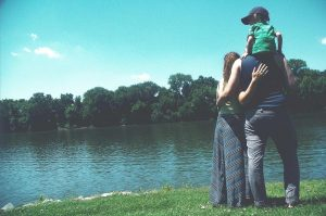 Two parents hold thier child on the shore of a lake. Be a better parent in recovery.