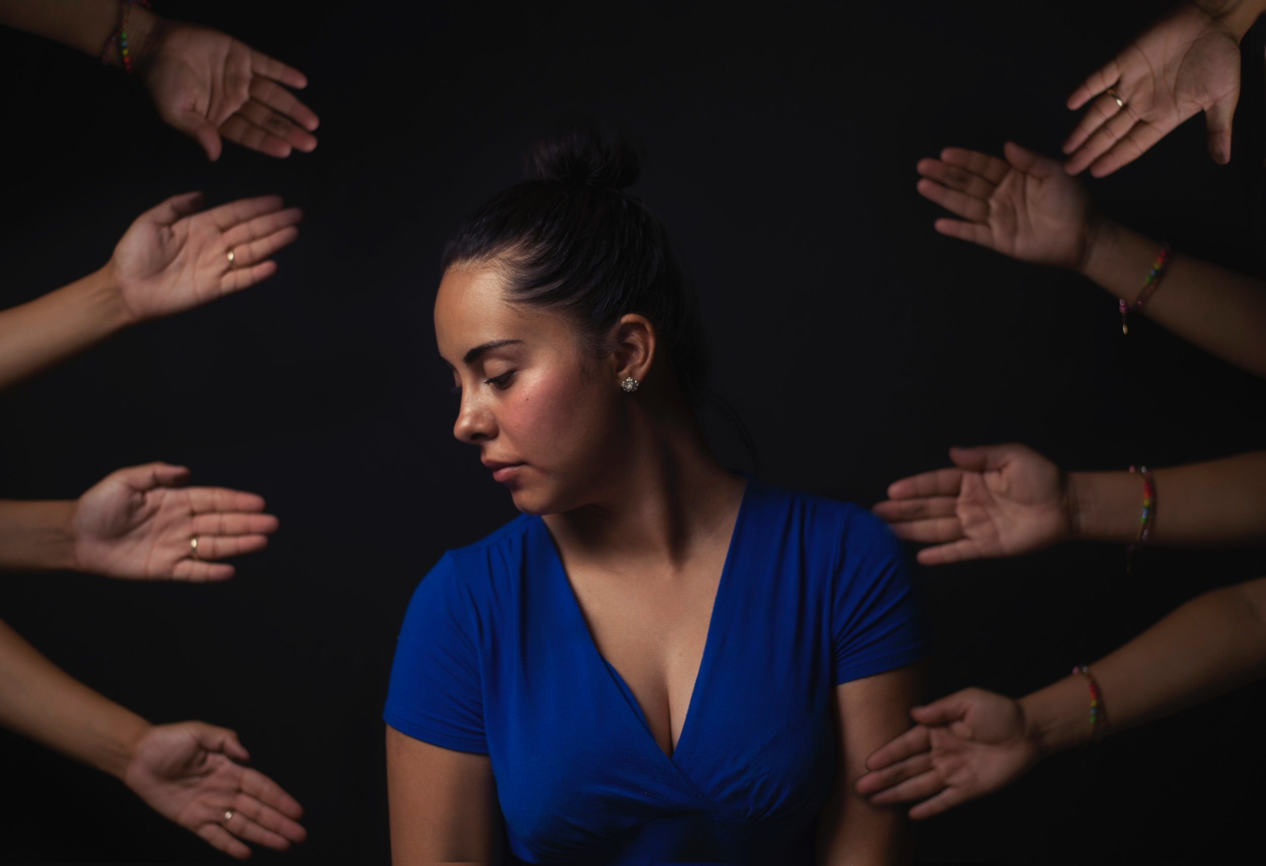 A woman sits in a dark space, with helping hands reaching toward her from all directions.