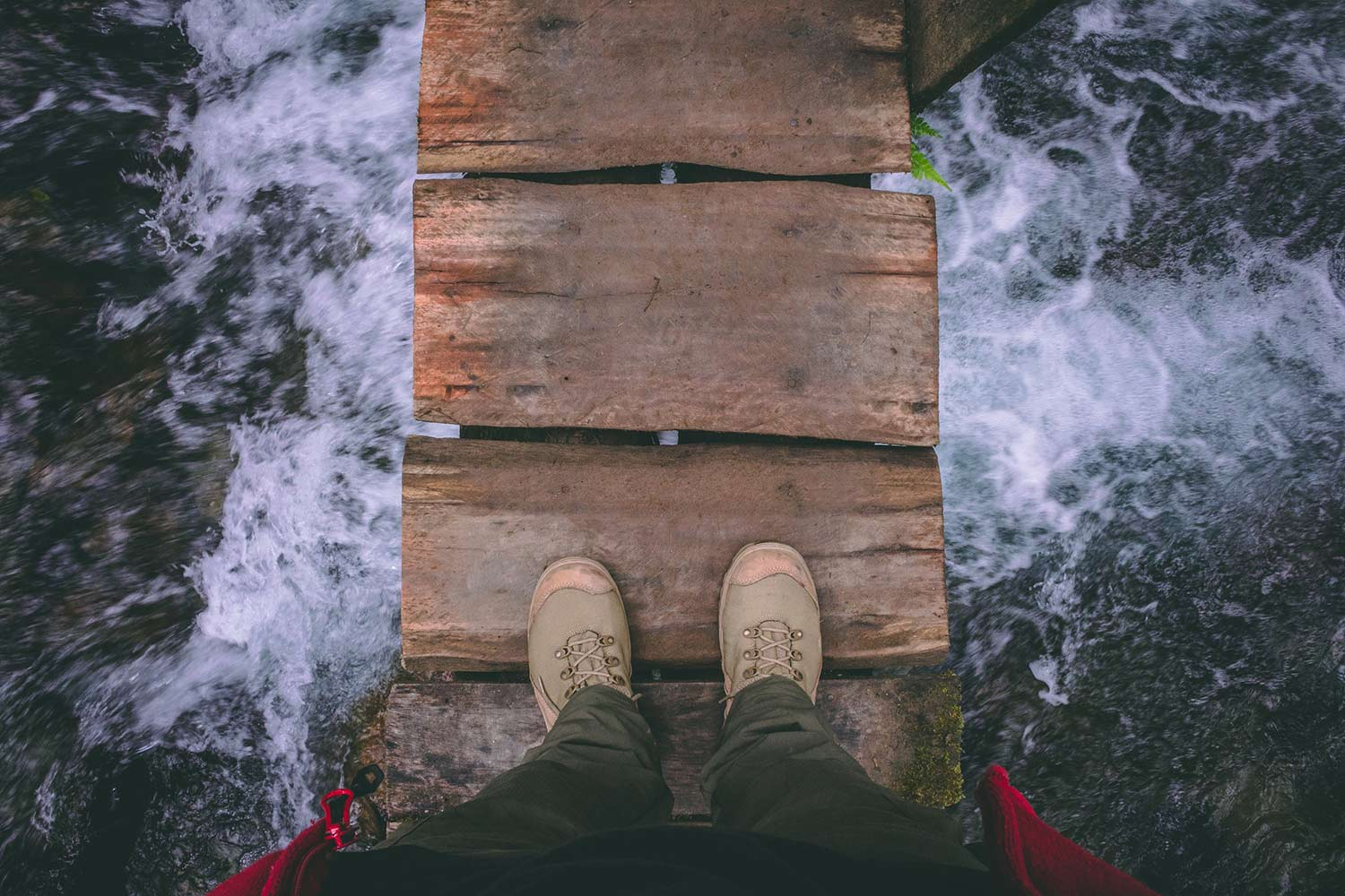 View down at a person's feet as they stand on a wooden plank bridge over a foaming river.