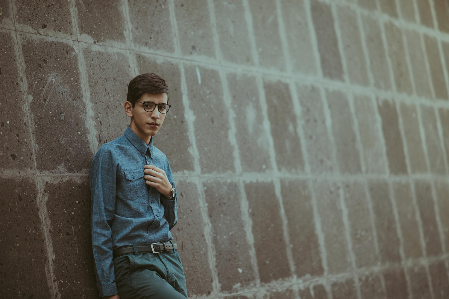 A teen boy in a blue button-up shirt leans against a concrete wall and stares warily at the camera.