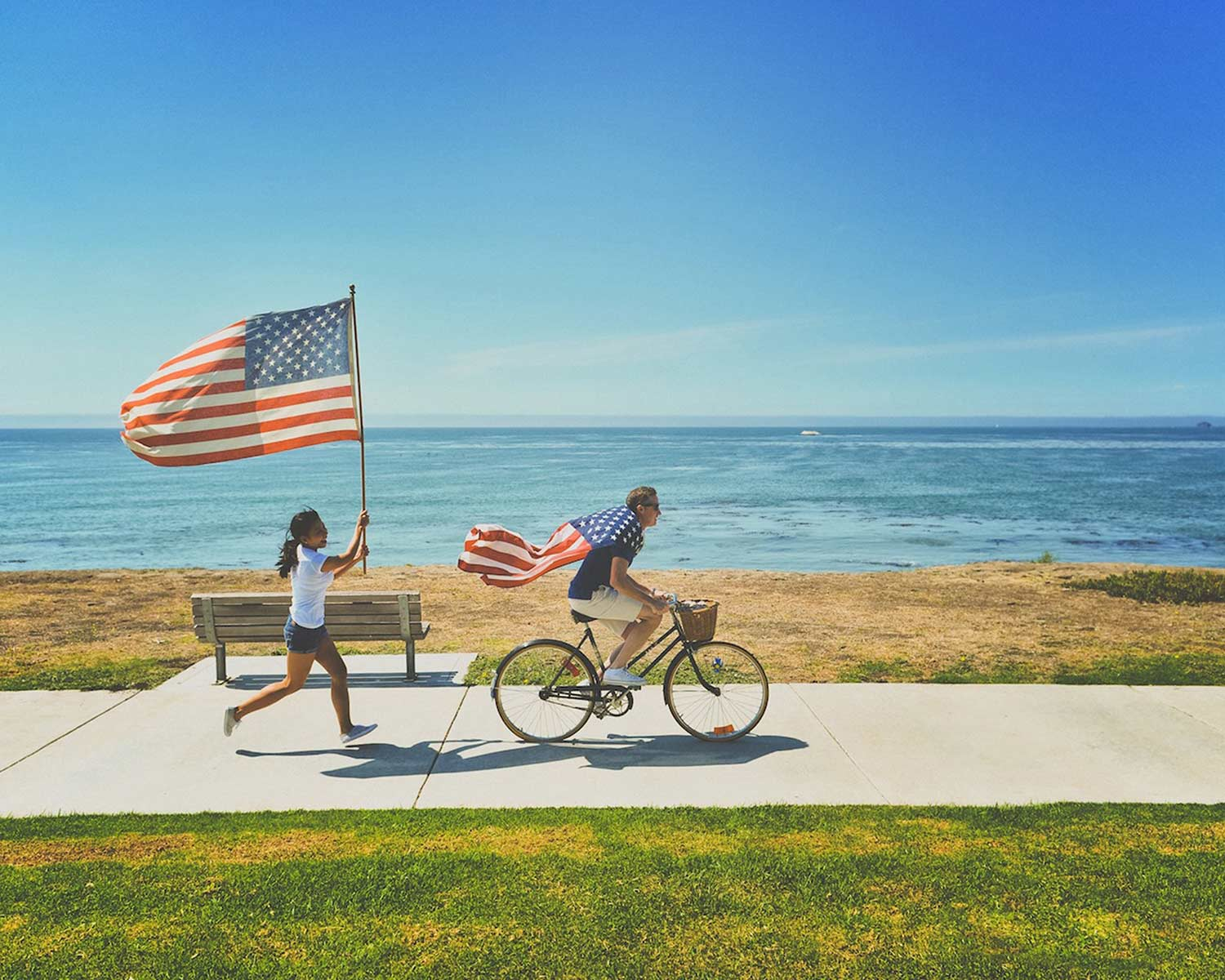 Beside the ocean, a man rides a bike with an American flag tied around his neck like a cape. Behind him, a woman runs with an American flag on a flagpole.