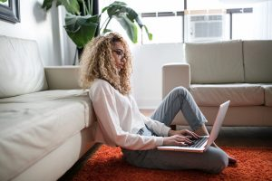 A woman sits on the floor with her laptop. Online addiction courses.