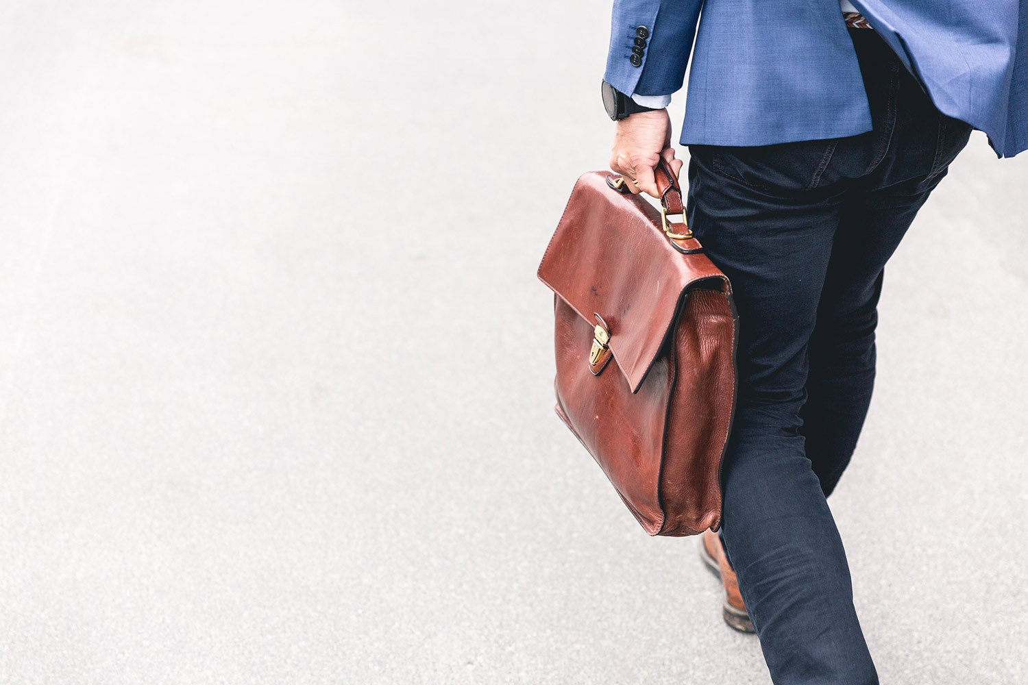 A man in business clothes carries a briefcase. Working when you're in recovery