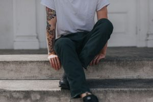 man-with-tattoos-sitting-on-steps