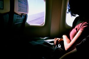 Woman looking out the window of an airplane. Business trips sober