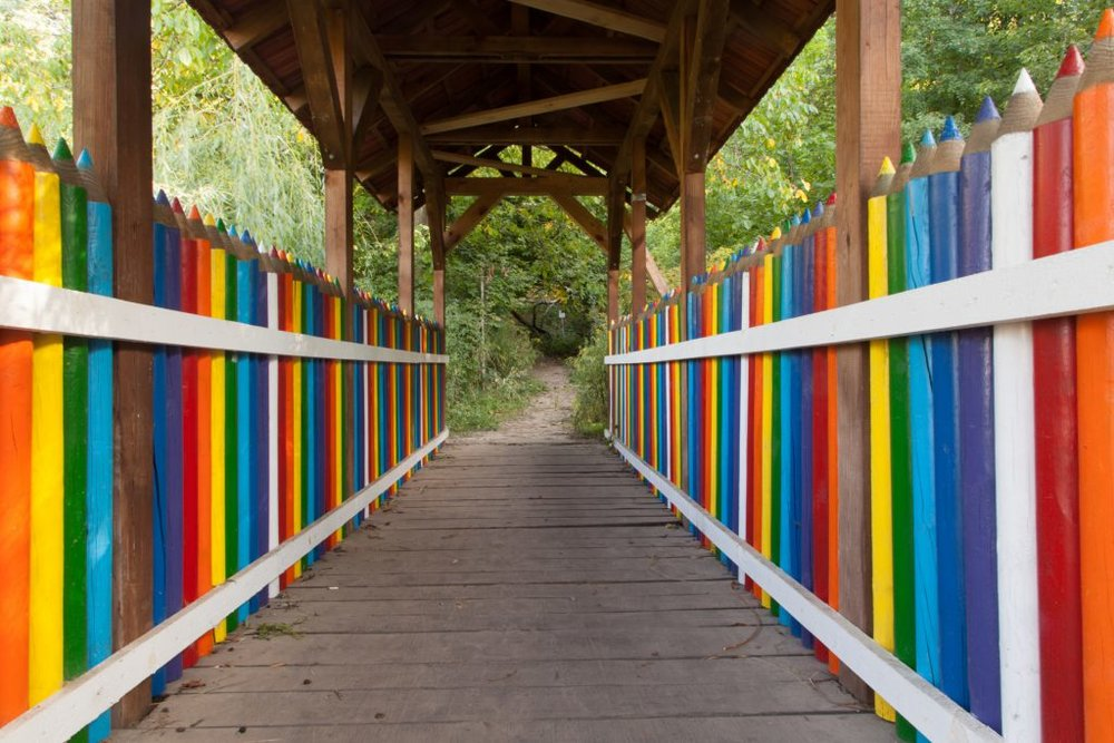 A covered bridge whose railings are shaped like colored pencils in rainbow colors.