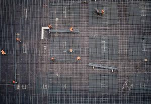 Aerial shot of construction workers laying rebar in a grid