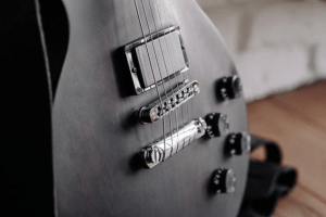Close-up photo of the belly of a black electric guitar