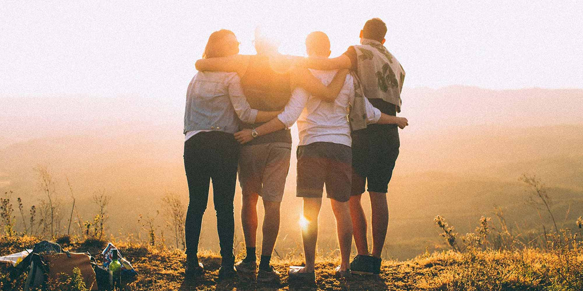 Four people with arms around one another stand atop a hill and look at the golden sunrise