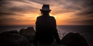 Rear view of a shadowed image. A woman in a hat stares out at the sunset.
