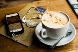 A latte next to an iPhone with earbuds. Recovery podcasts