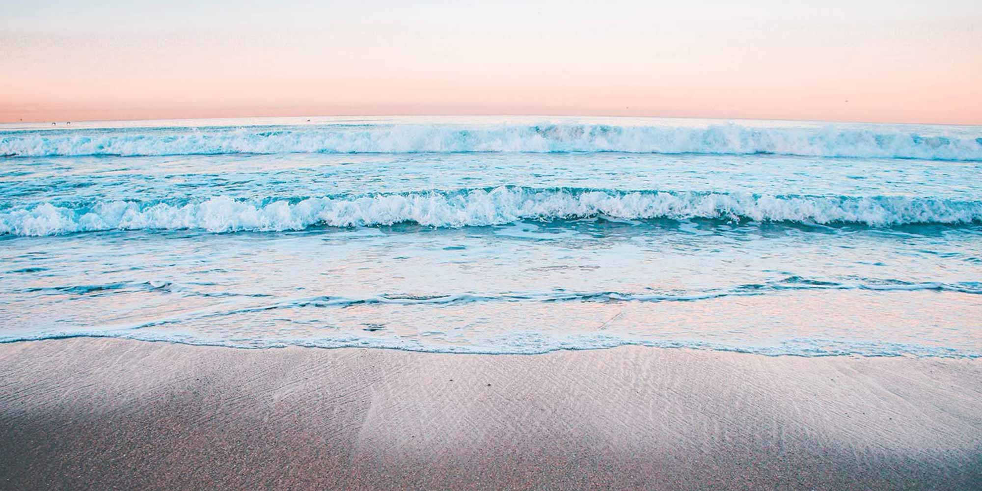 A peaceful beach at sunrise, with a pastel sky.