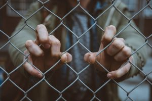 A man behind a fence grips the chain links tightly. Prison system opioid epidemic