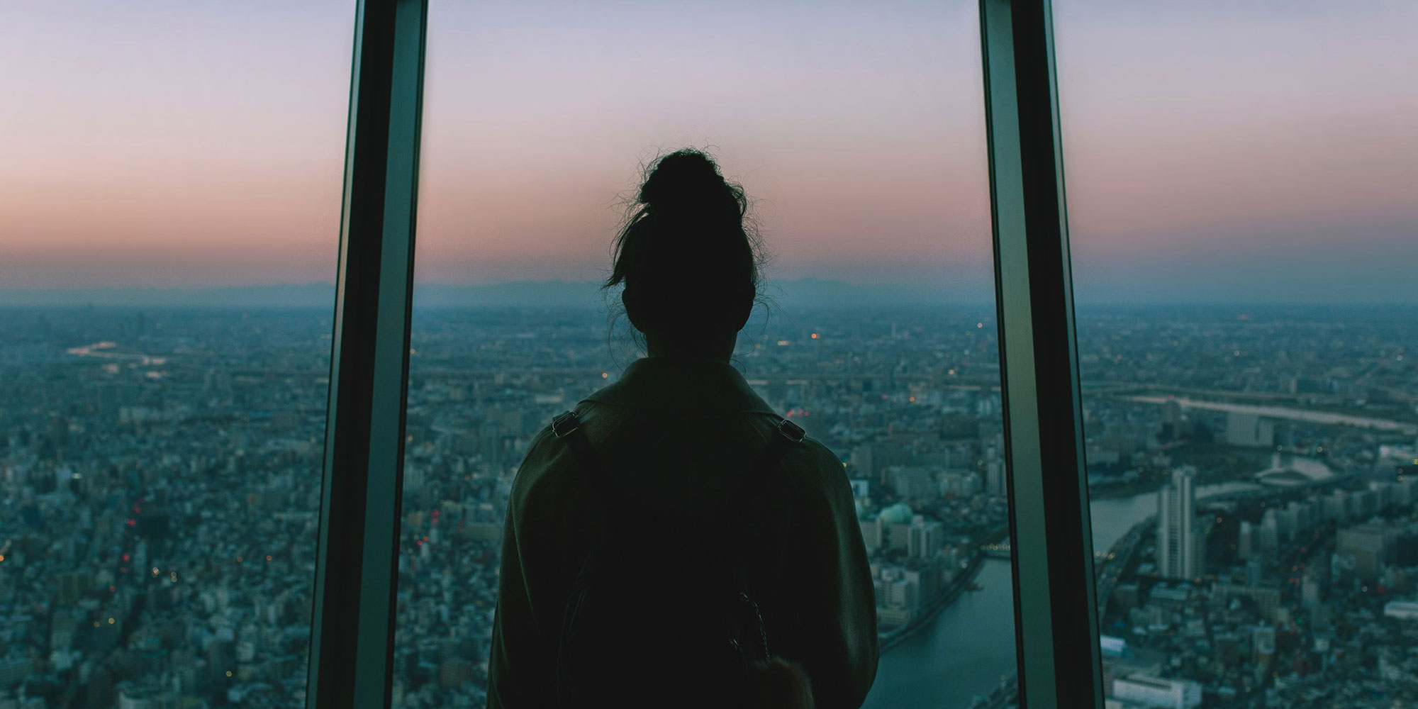 Back view of a person staring out a window