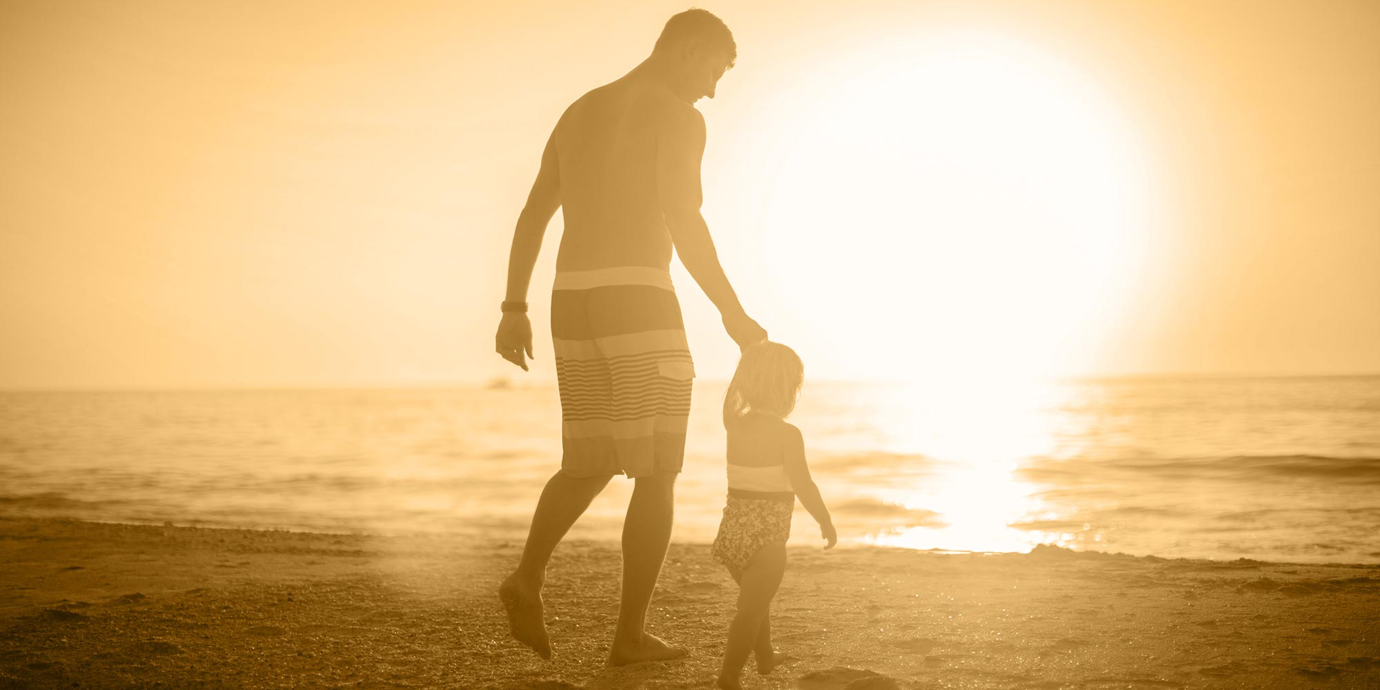 Father and small child walking on the beach
