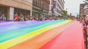 A rainbow flag fills the street at a Pride event