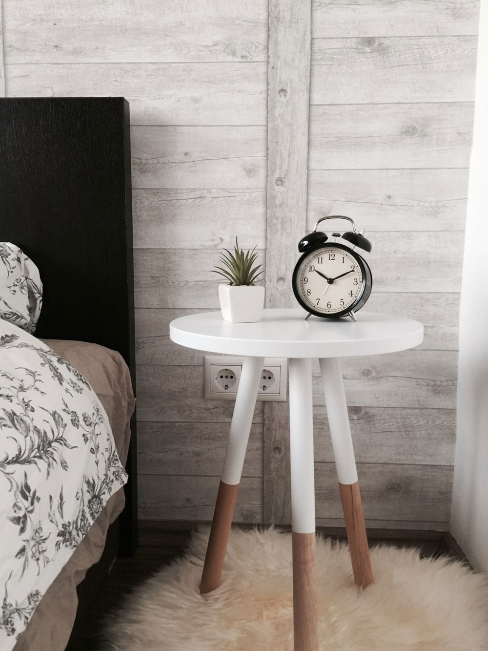 An old fashioned alarm clock on a bedside table beside a potted succulent