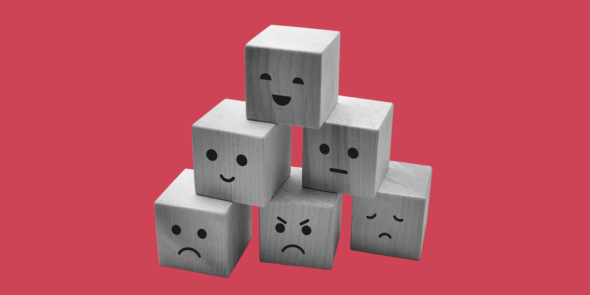 A stack of wooden children's blocks with facial expressions painted on them