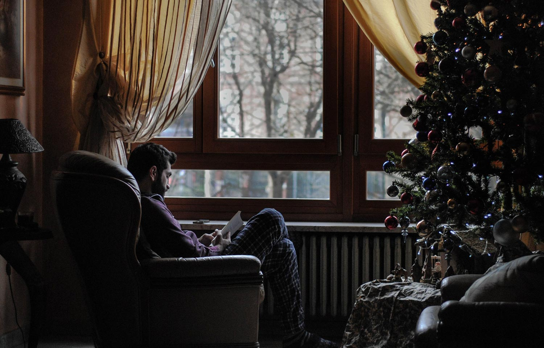 man-reading-christmas-tree