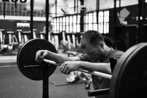 In a gym, a man leans his arms against a barbell loaded with weights
