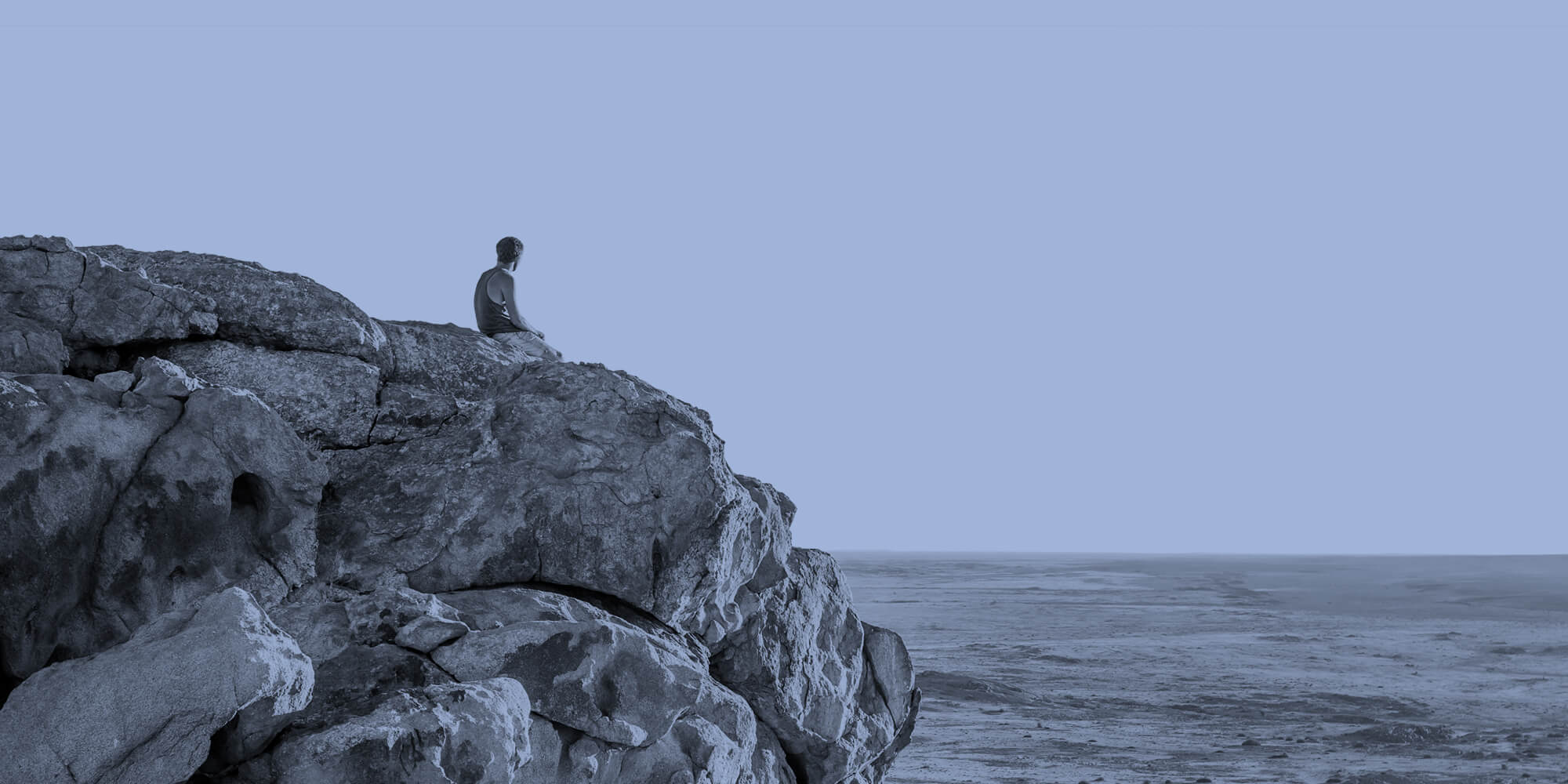 Sitting alone on a rock, looking at the ocean.