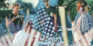 People at an outdoor barbecue. The image is overlaid with American flags.
