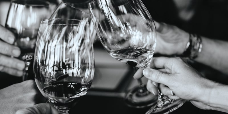 Hands of several friends clinking wine glasses together