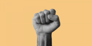 Fist of a Black individual thrust upwards.