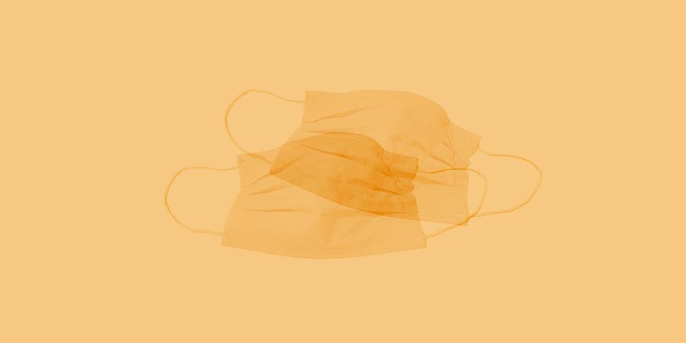 Two medical face masks on a orange background.