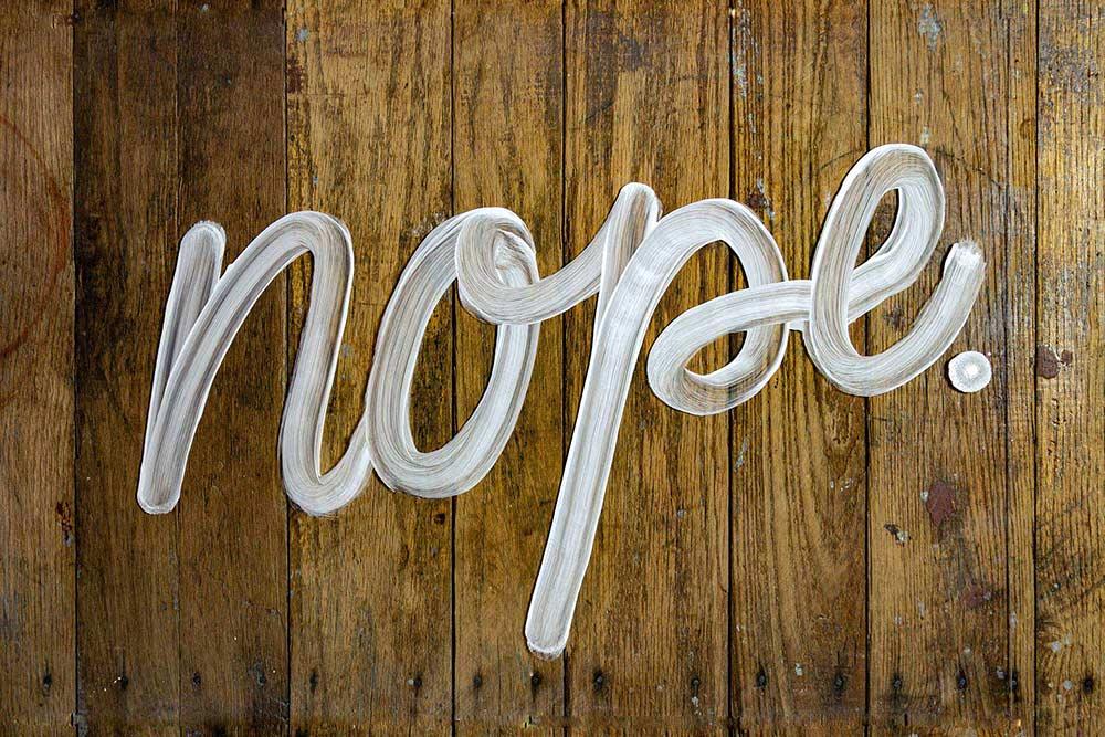 "The cursive word ""Nope."" written in shaving cream on a wooden floor"