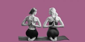 Two women kneel next to one another on mats, doing yoga