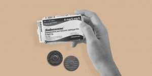 Hand holding a packet of Suboxone, with two sobriety chips in the background. Can Suboxone and the 12 steps work together?